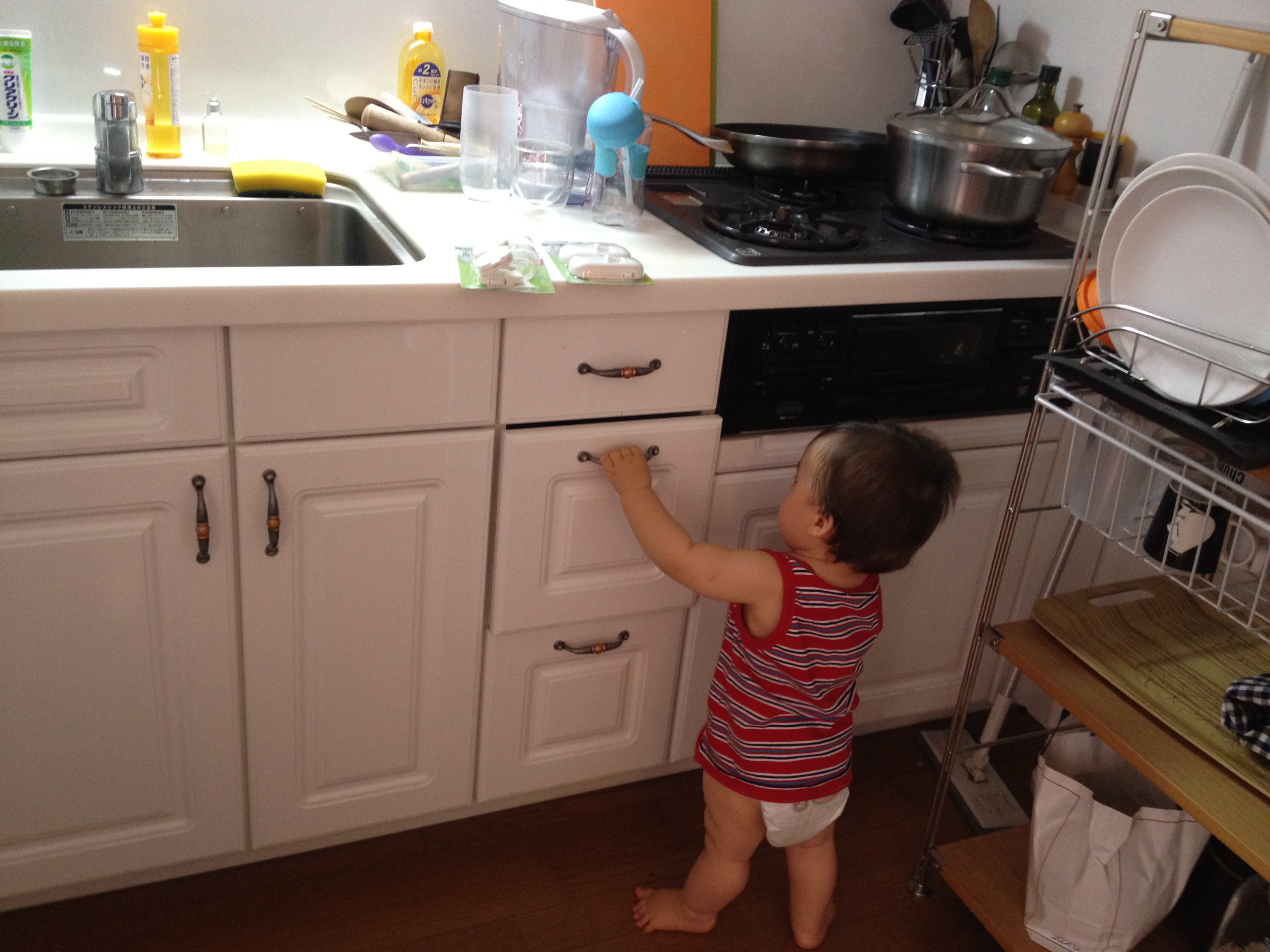 Baby trying to open kitchen cupboards - Tokyo Urban Baby